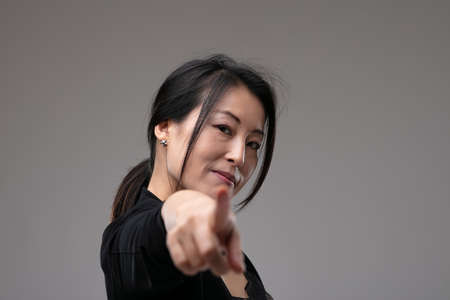 Woman pointing at the camera in blame or identification pr expressing a choice with a serious thoughtful expression over a grey studio background with copyspace
