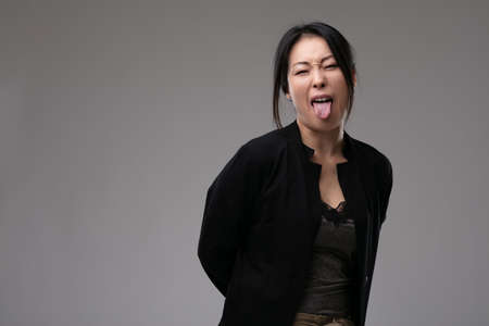 Sassy rude Asian woman sticking out her tongue as she looks at the camera over a grey studio background with copyspace Foto de archivo