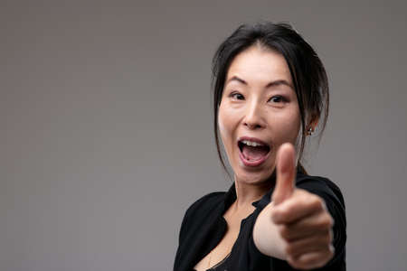 Enthusiastic Asian woman cheering giving a thumbs up gesture of success and achievement over a grey studio background with copyspace with focus to her face