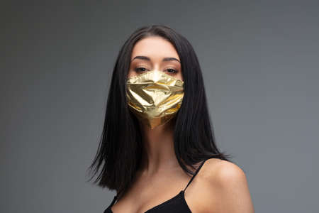 price rise of face masks and scarcity in times concept as a beautiful young woman wearing a face mask made of gold because she can afford it even if they are become an extremely rare good