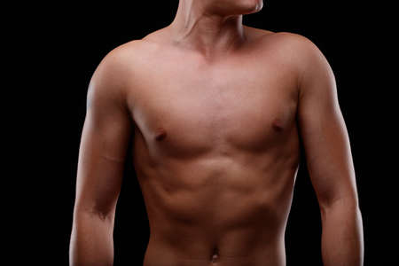 Front close up view of the chest of an athletic toned young man over a black background