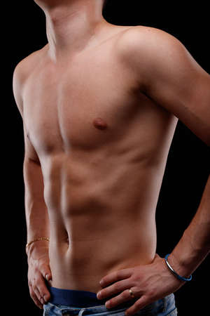 Sexy sporty young man posing shirtless in a cropped three-quarter turned portrait with hands on hips showing off his flat toned abdomen and pectorals Foto de archivo
