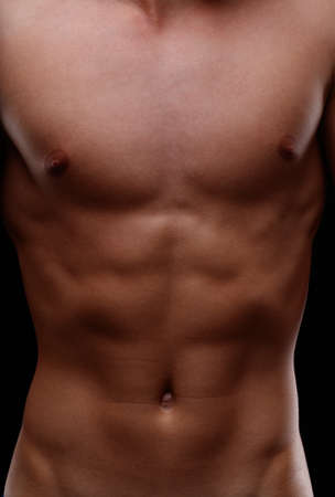 Close up on the muscular flat toned torso of an anonymous young fit healthy man in a shadowy frontal full frame portrait