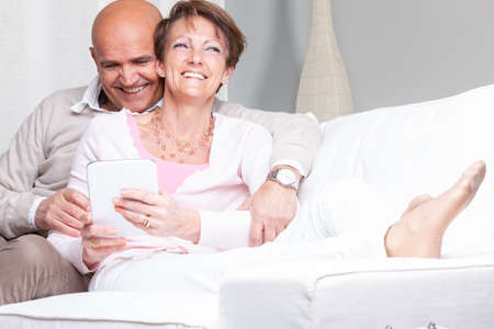 Attractive vivacious middle-aged couple relaxing at home on the couch in a close embrace as they share the media on a tablet-pc grinning happily in amusement