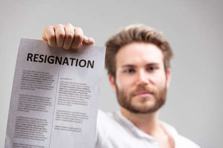 Bearded young man holding up a resignation letter to the camera with large heading and blurred text in a conceptual employment and work image