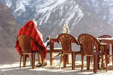 Sherpa (porter) warming up in the sunrise after a cold night at the Annapurna Base Camp, Nepal Stock Photo