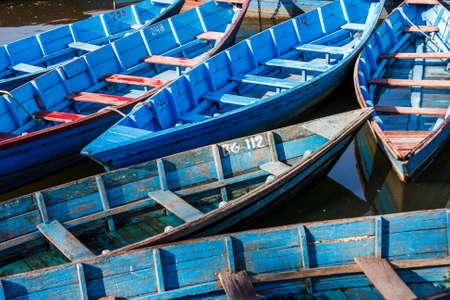 Small wooden colored boats on the Phewa Lake, Pokhara, Nepal