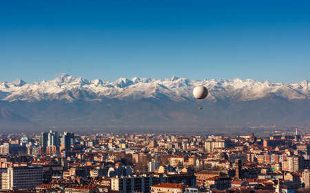 collina: Panorama of Turin, with the Alps in the backround and a hot air baloon, Turin, Italy