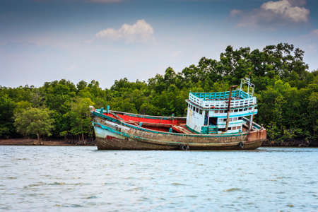 Half sunk shipwreck leaning on one side in Krabi, Thailand
