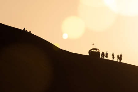 Silhouettes of tourists with a a dune buggy in the desert in Huacachina, Ica, Peru
