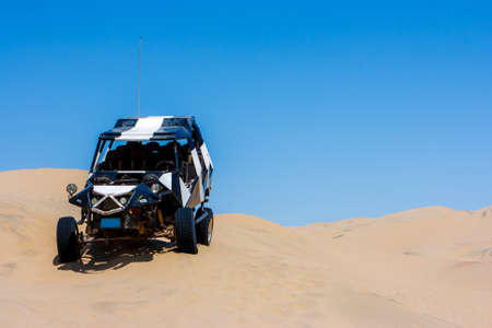 Dune buggy over a sand dune with blue sky in the desert, Huacachina, Ica, Peru 版權商用圖片 - 145204641