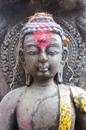 Detail of a Buddha statue with Tikka, colored powder, in Kathmandu, Nepal