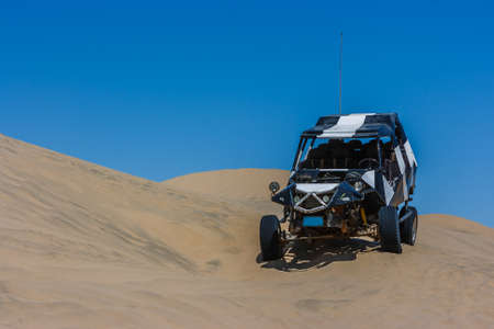Dune buggy over a sand dune with blue sky in the desert, Huacachina, Ica, Peru