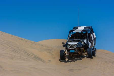 Dune buggy sur une dune de sable avec ciel bleu dans le désert, Huacachina, Ica, Pérou Banque d'images