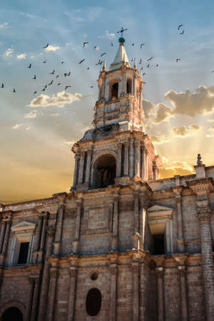 View of the bell tower of the Arequipa cathedral, Peru at sunset with birds