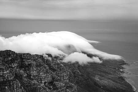 Scenic view of the clouds rolling over Table Mountain in Cape Town, Southafica. This fenomenon is called Tablecloth. 版權商用圖片 - 140260776