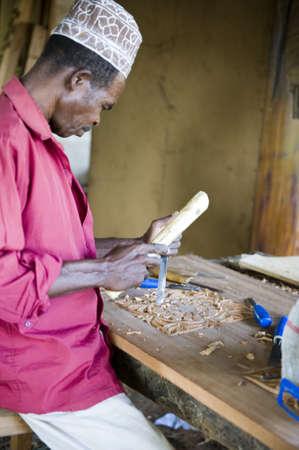 trinchante: Zanzíbar, Tanzania - el 27 de febrero de 2008: Un tallador de madera local que trabaja en un pueblo del interior Editorial