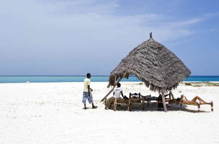 local 27: Zanzibar, Tanzania - February 27, 2008: Northern coast, local young servant and a tourist on the  beach