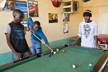 september 2: Aruscha, Tanzania - September 2, 2008: Young local people playing in a tavern of the general market Editorial