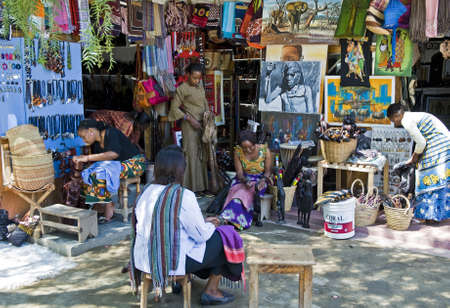 september 2: Aruscha, Tanzania - September 2, 2008: Local women  between crafts and paintings of the Masai Market