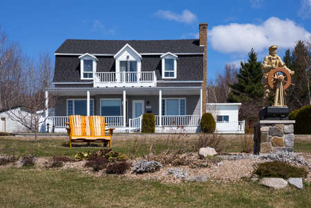 Tedoussac,  Canada - May 8, 2014: Quebec,  a house of the village with a sailor statue