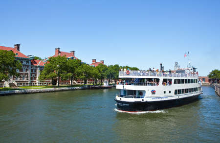 ellis: New York, U.S.A. - July 12, 2009: A ferry with tourists near Ellis Island Editorial