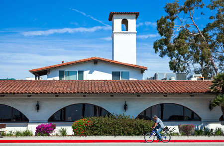 barbara: Santa Barbara,  U.S.A. - June 1, 2011:  A man in bycicle in front of a traditional house on the sea front