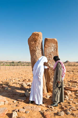 standing stone: Al Jouf,  Saudi Arabia - November 26, 2008: Local people in the  Rajajil archaeological site with the prehistoric standing stone.