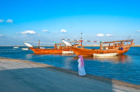 dow: Dammam, Saudi Arabia - November 16, 2008:  A local man walking in front of the Dow boats in the fisherman area. Editorial