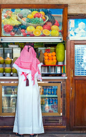 souk: Dubai, U.A.E. - February 17,  2007:  A man in traditional dress at a fruit and juice shop in the old souk
