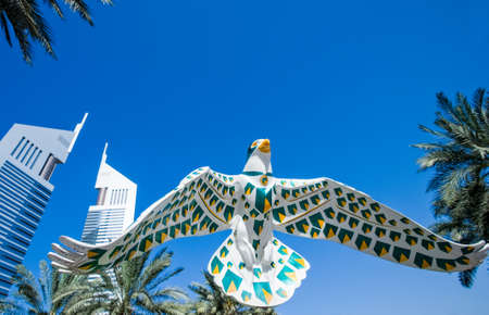 sheik: Dubai, U.A.E. - February 18,  2007: A falcon sculpture between the architectures of the business area of the  Sheik Zaied Road. In the background The Emirates Towers.