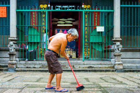 sweeps: Hong Kong, China - September 25,  2007: An old man sweeps the entrance of the Tin Hau Temple in the Yau Ma Tei quarter.