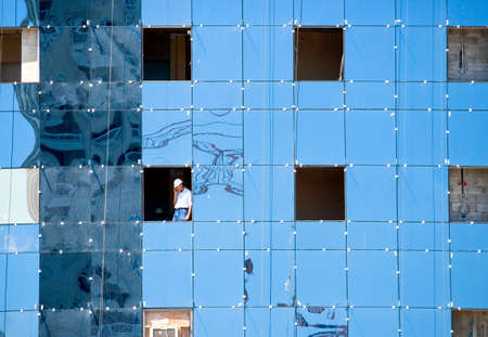 costruction: Doha,  Qatar - April 10, 2006:  A worker in a window phoning in a costruction site of the business area