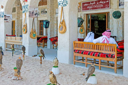 falconry: Doha,  Qatar - February 14, 2006: Local people and falcons in the Souq Wakif in the old city center