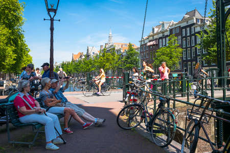 red light district: Amsterdam, Holland - July 22, 2014: Red Light district. local people and tourists relaxing near a traditional drawbridge Editorial