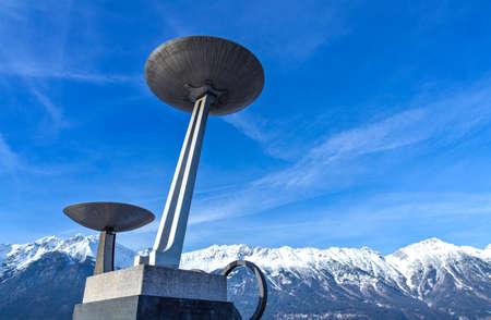 deportes olimpicos: Innsbruck, Austria - el 8 de febrero de 2010: Los braseros Olímpicos de estadio de Bergisel el skijamping con las montañas nevadas en el fondo