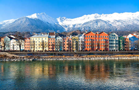 tyrol: Austria, Tyrol, Innsbruck, the Mariahilf strasse colored houses on the Inn river with the snowy mountains in the background