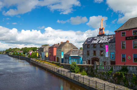 housed: Kilkenny,  Ireland - August 2, 2013:  Colored houses of the old town seen from the John bridge on the Nore river