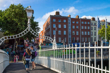 liffey: Dublin,  Ireland - July 31, 2013:  Young people on the Hapenny bridge on the Liffey river, Temple Bar district Editorial