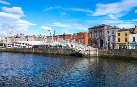liffey: Dublin,  Ireland - July 31, 2013:  The Hapenny bridge on the Liffey river, Temple Bar district Editorial