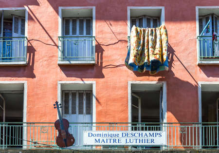cellos: Toulon, France - June 27, 2009: The facade of a house of the old country center with the advertising of a cellos artisan.