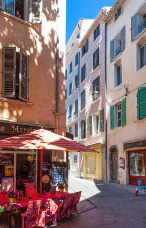 toulon: Toulon, France - June 27, 2009: An alley of the old country center with a full color restaurant in the foreground. Editorial
