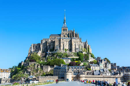 michel: Mont St. Michel, France - May 22, 2012: Normandy, people walking towards the entrance of the medieval village and abbey. Editorial
