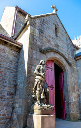 st michel: Mont St. Michel, France - May 22, 2012:  Normandy, the St Peter statue and church in the medieval village.