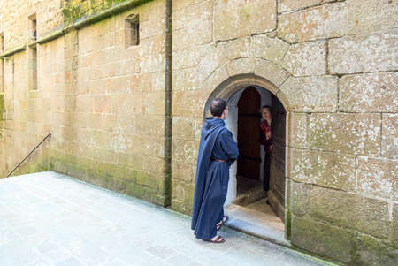 st michel: Mont St. Michel, France - May 22, 2012: Normandy,  a monk in front of a door of a house in the ascent to the abbey Editorial