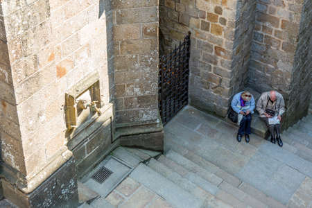 ascent: Mont St. Michel, France - May 22, 2012: Normandy, tourists in a moment of rest in  the ascent to the abbey.