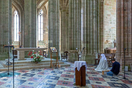 st  michel: Mont St. Michel, France - May 22, 2012: Normandy, a nun in prayer in the church of the abbey