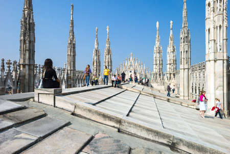 Milan, Italy - April 21, 2011: People between the spires and marle works of the Duomo cathedral rooftop Stock Photo - 56983277