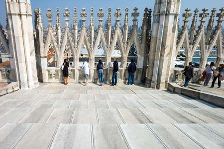 Milan, Italy - April 21, 2011: People between the spires and marle works of the Duomo cathedral rooftop Stock Photo - 56983278