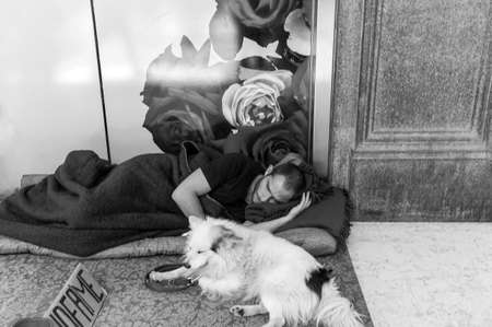 shopwindow: Milan, Italy - July 5, 2014: An  homeless man with his dog, sleeping in front of a shopwindow  in Corso Vittorio Emanuele